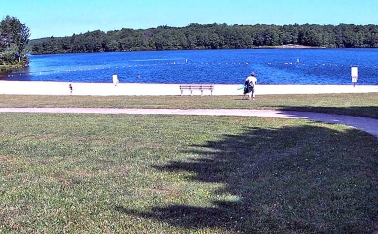 man on shore heading for lake