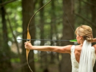 bride in the woods aiming bow and arrow