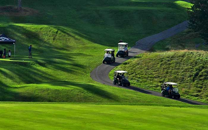 four golf carts going up the hill