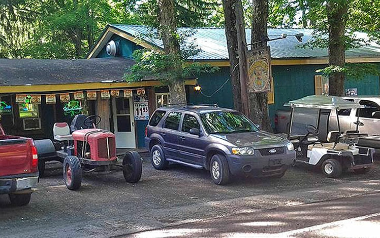 exterior of building and parking lot with tractor and golf cart