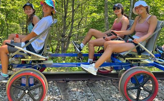 4 people on tandem bike on railroad tracks