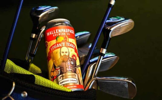 Wake Zone Indoor Golf + Taproom can of beer and golf bag