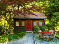 red and brown cottage with patio and table