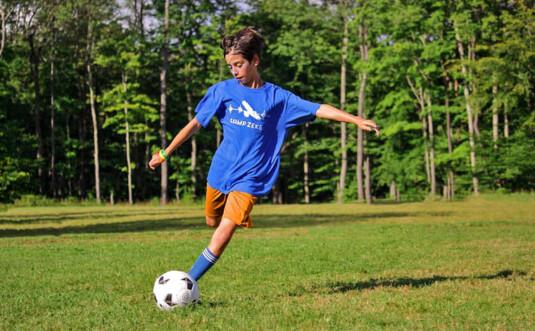 camper kicking the soccer ball
