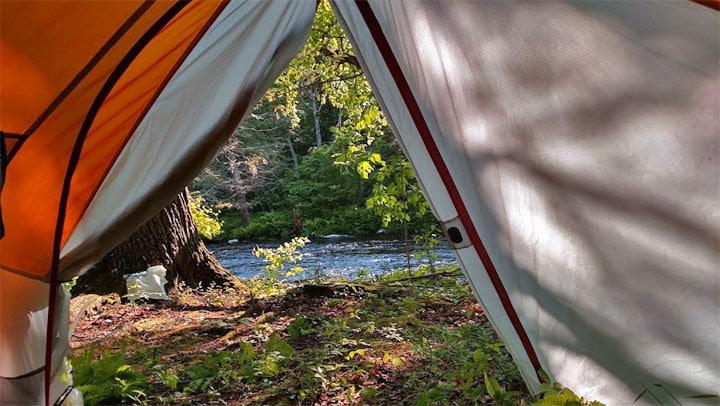 camping tent in the woods overlooking the stream