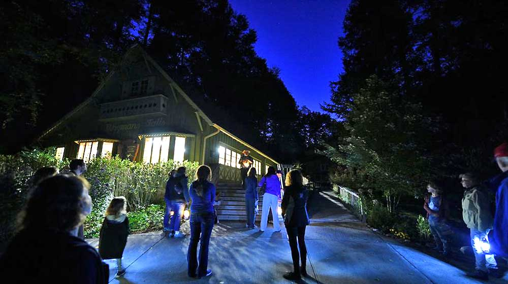people in front of dingmans falls visitors center at night