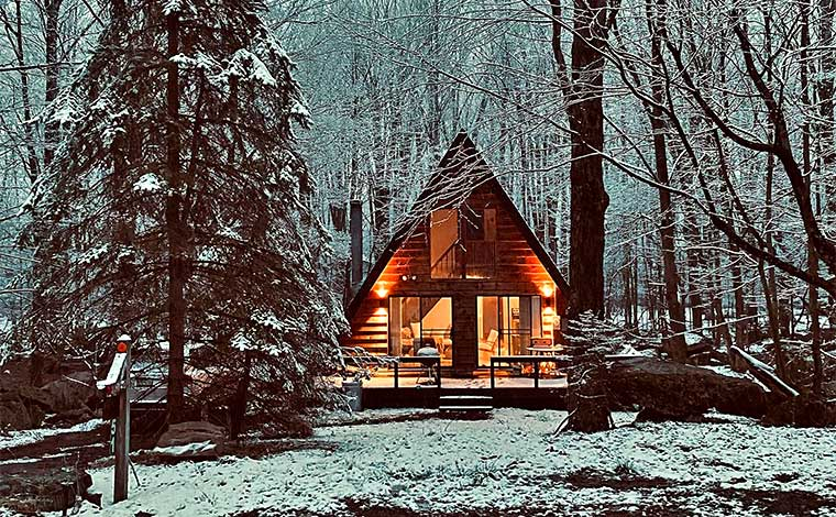 exterior a-frame cabin in the woods in winter snow