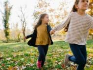 2 kids running through a field