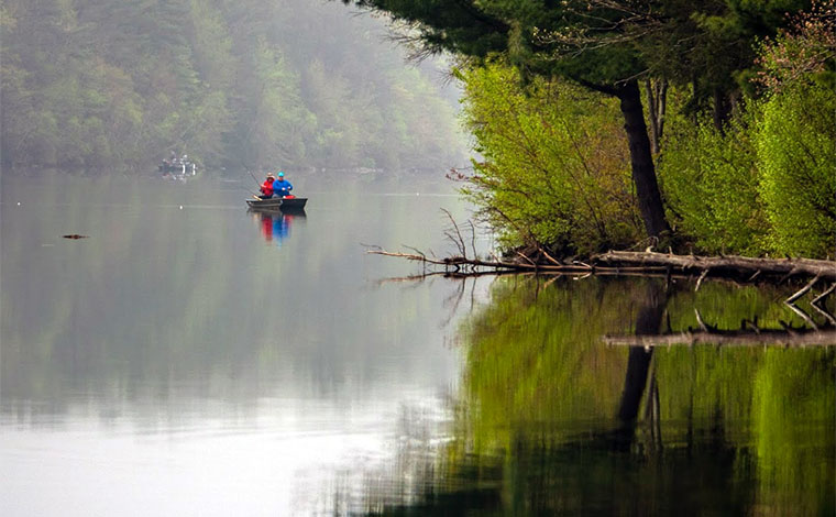 couple fishing on a foggy lake