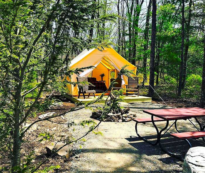 glamping tent site with picnic table and firepit