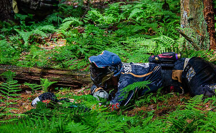 skirmish paintball player crouching in field