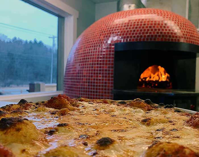 wood fired oven and whole pizza