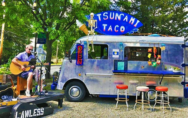 food truck with musician performing next to it